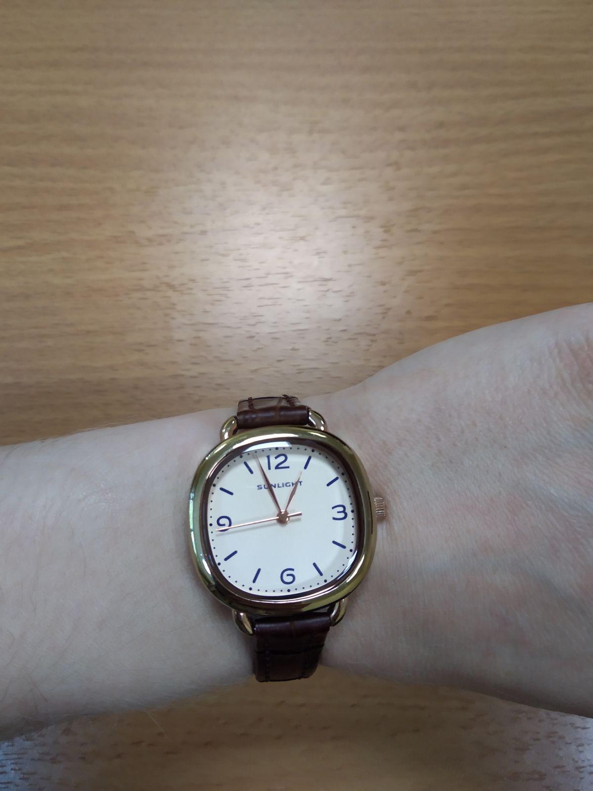 Часы в золотой оправе с круглым циферблатом на красном кожаном ремешке